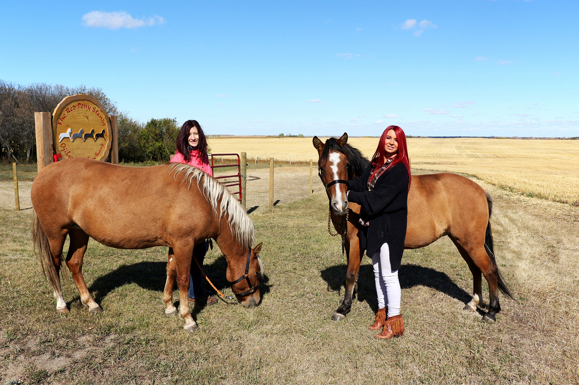 Two women stand with two horses in front of The Red Pony Stands® entrance sign