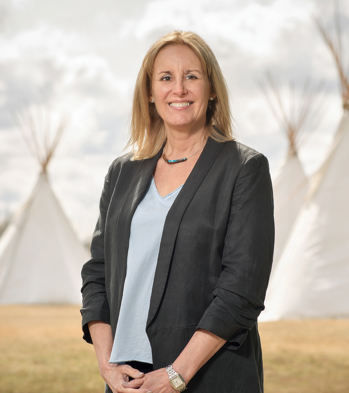 Woman in business attire in front of teepees