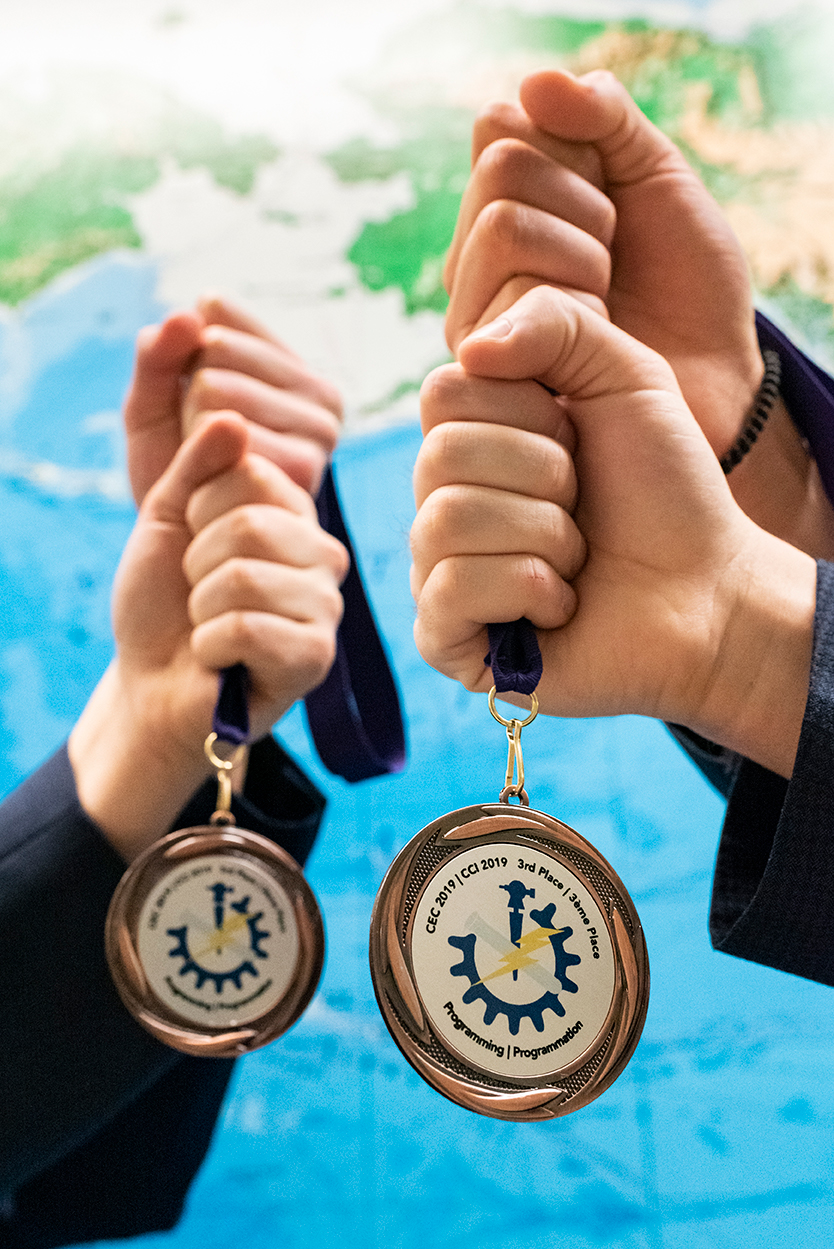 Two hands holding medals