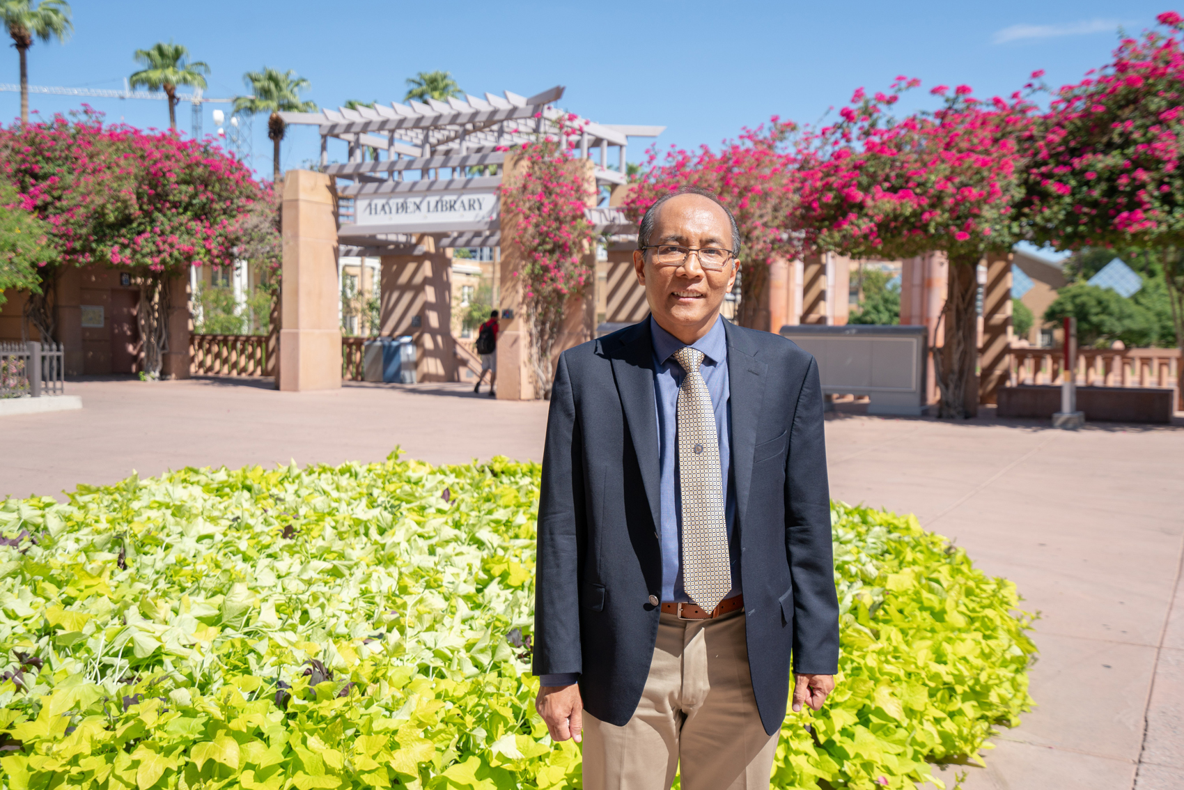 Soe Myint outside on a summer day, surrounded by greenery, andin front of the Arizona State University library.