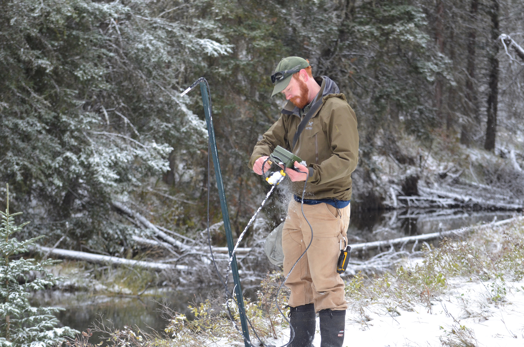 Adam Sprott checking bat detectors in on a snowy day.