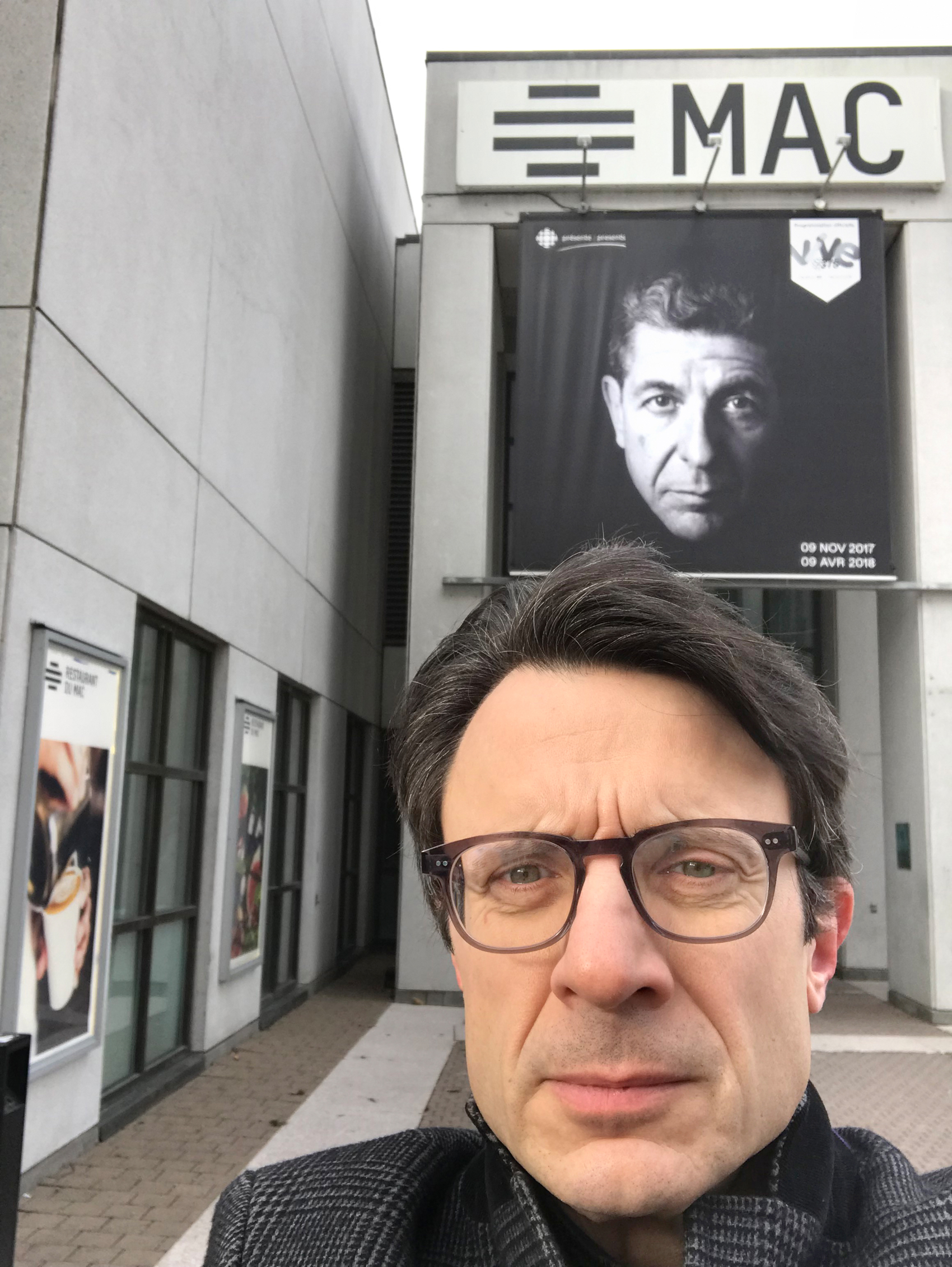 Thomas Hadjistavropoulos poses for a selfie outside of the Montreal Museum of Contemporary Art. A poster of Leonard Cohen, his famous idol, is in the background.
