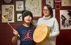 Natalie Owl and her nine-year-old son, Isaac, who is playing a traditional drum and singing a prayer song for healing. Owl is holding a book she co-wrote with her mother, Maryann Owl, which features Isaac and teaches the Nishnaabemwin language.