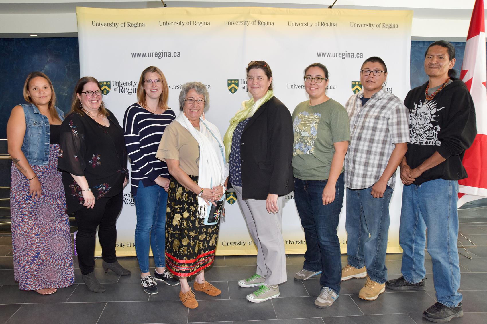 Six individuals standing against the Universit of Regina media wall.