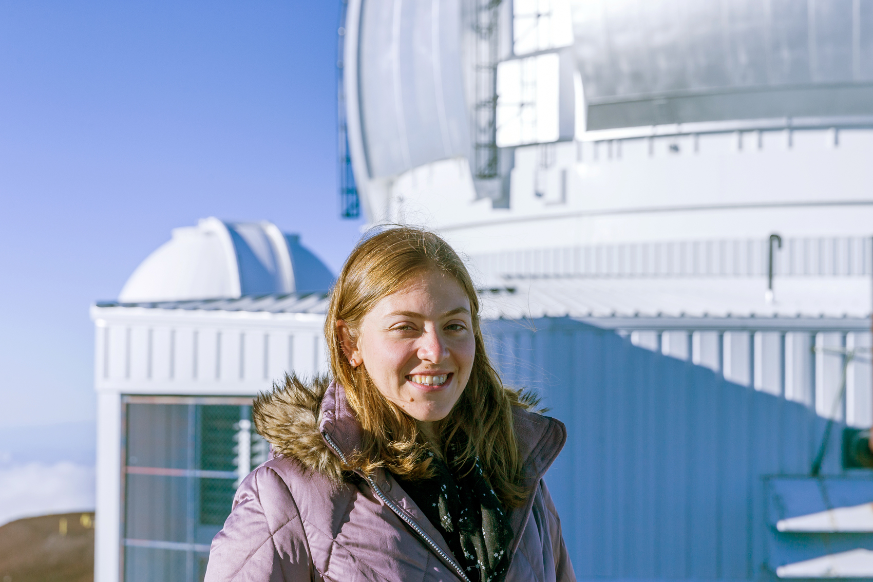 Astronomer Rosemary Pike at the Gemini Observatory on Maunakea in Hawaii. The Gemini telescope dome is behind Pike, and the Canada-France-Hawaii Telescope is the smaller dome to the lower left.