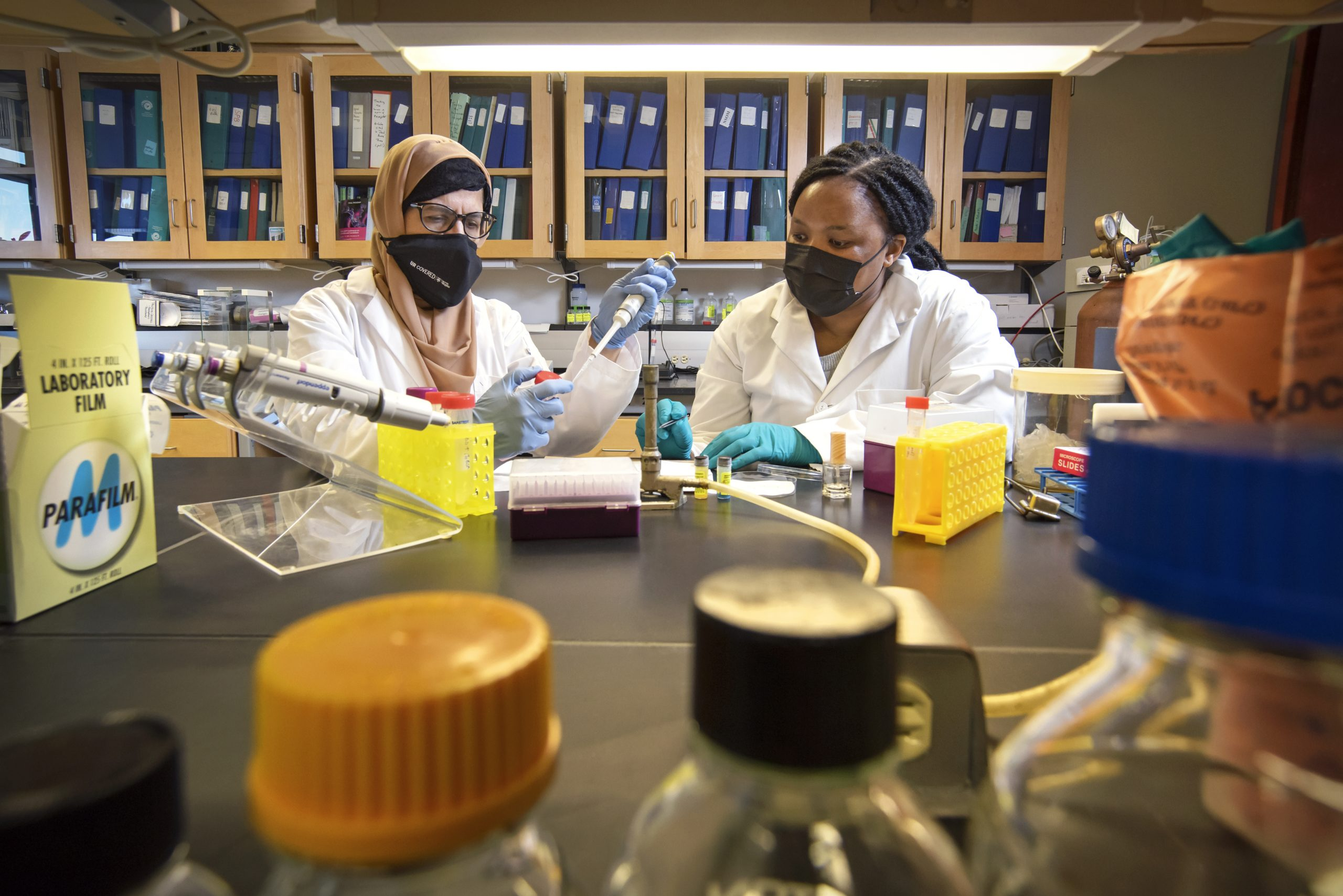 Research associate Dr. Taranum Sultana and Easter Ndlovu, a doctoral candidate in chemistry and biochemistry, working in a U of R lab.  (Photo by Trevor Hopkin)