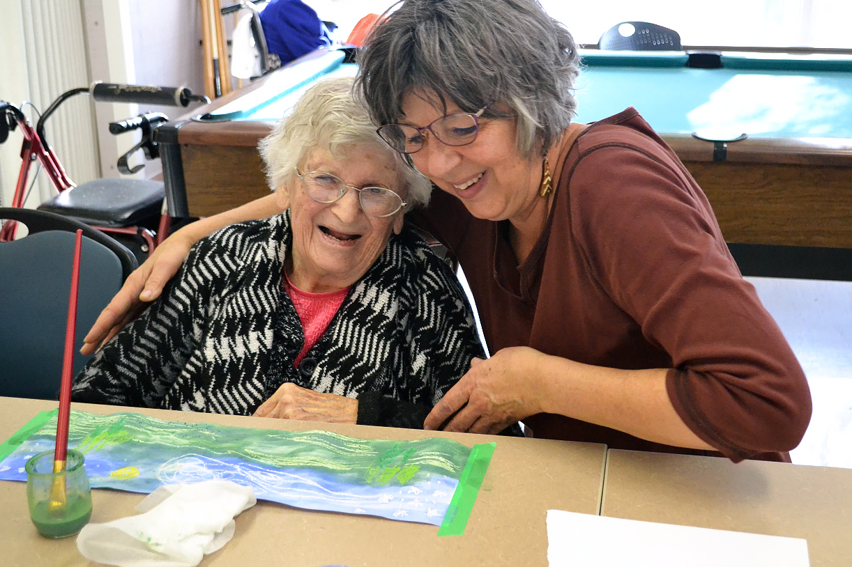 Visual artist Shon Profit at the Eastend long-term care centre teaching expressive art to 93 year-old Dorothy Armstrong. This photo was taken pre-COVID. (Photo by Kathy Berquist)